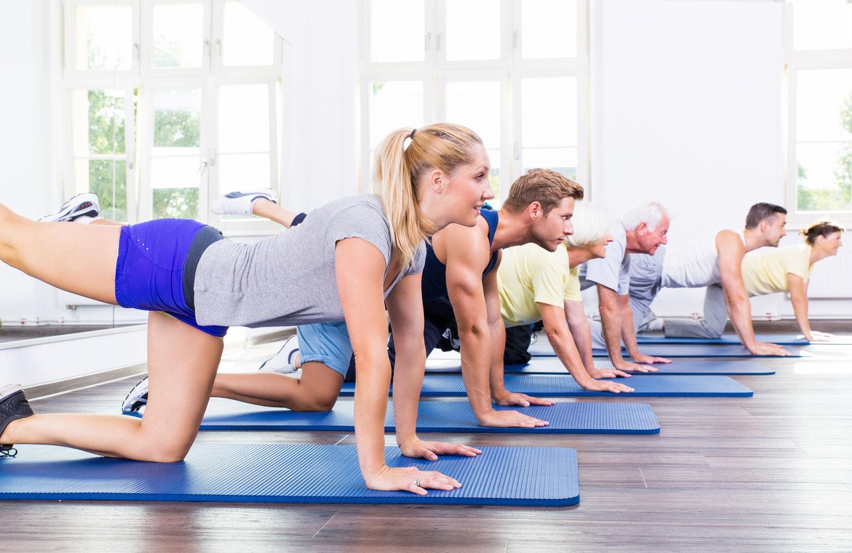 Gruppe bei Gymnastikübung auf Sportmatten