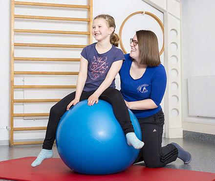 Mädchen auf blauem Gymnastikball mit Physiotherapeutin während Physiotherapie