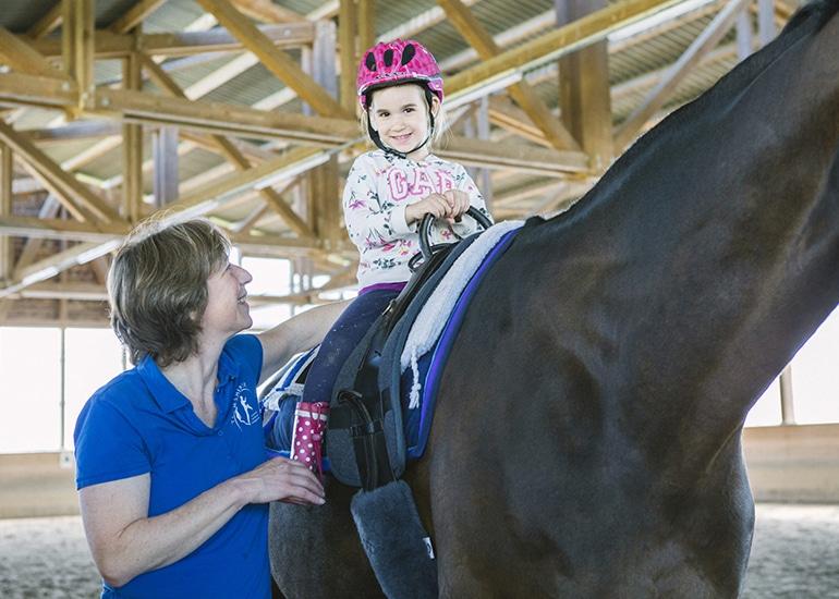 Kind auf Pferd mit Therapeutin