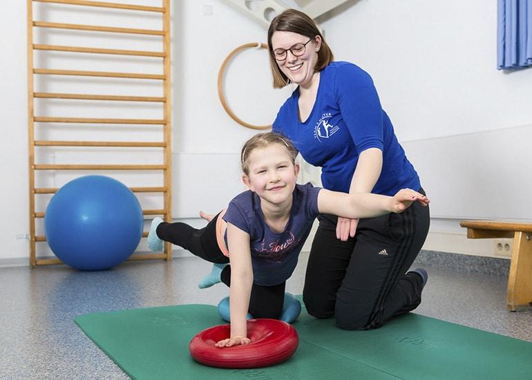 Mädchen und Physiotherapeutin bei der Physiotherapieübung auf Balance Pad