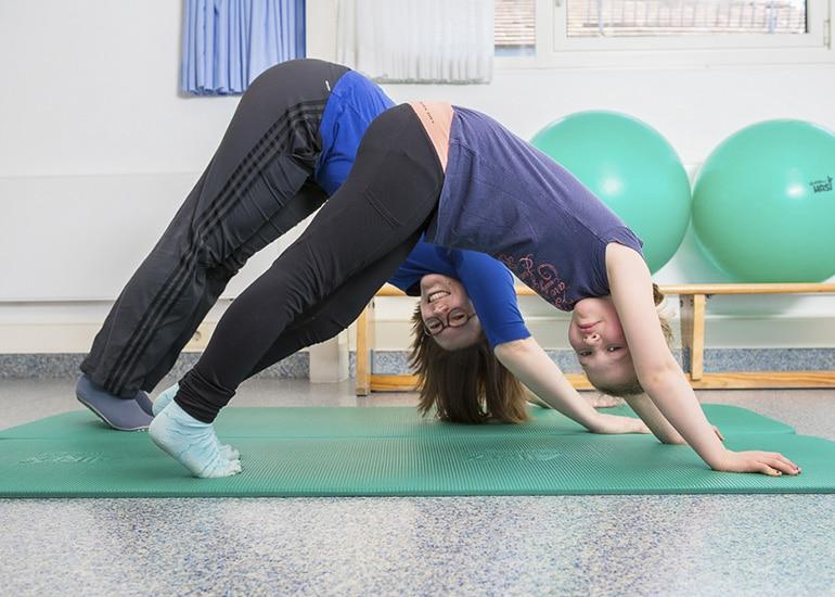 Kind macht Physiotherapieübung mit Füßen und Händen mit Physiotherapeutin auf Sportmatte