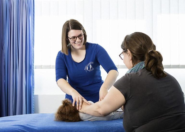 Physiotherapeutin mit Mutter und kleinen Kind bei der Vorschau für Übungen