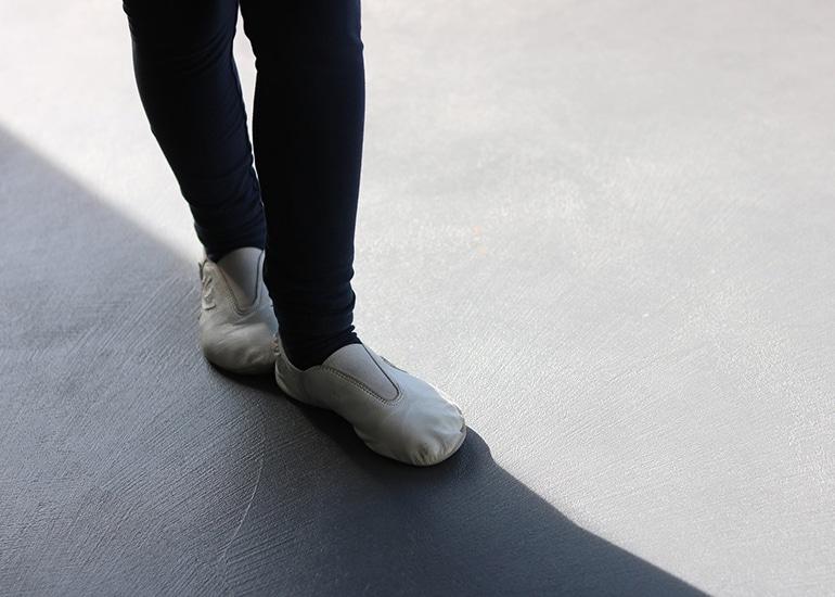 Kind balanciert auf Schatten mit Gymnastikschuhen