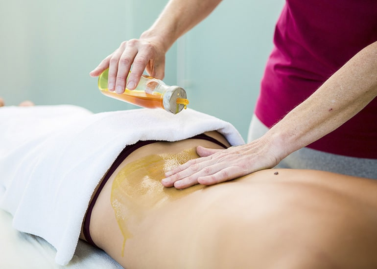 Ayurveda Anwedungen und Massage bei Team Sabine Herter in Gerlingen durch Mitarbeiterin mit feinem Öl auf Haut der Patientin