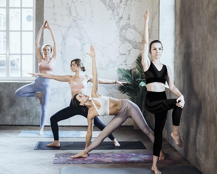 Frauen machen in der Gruppe verschiedene Yoga-Übungen