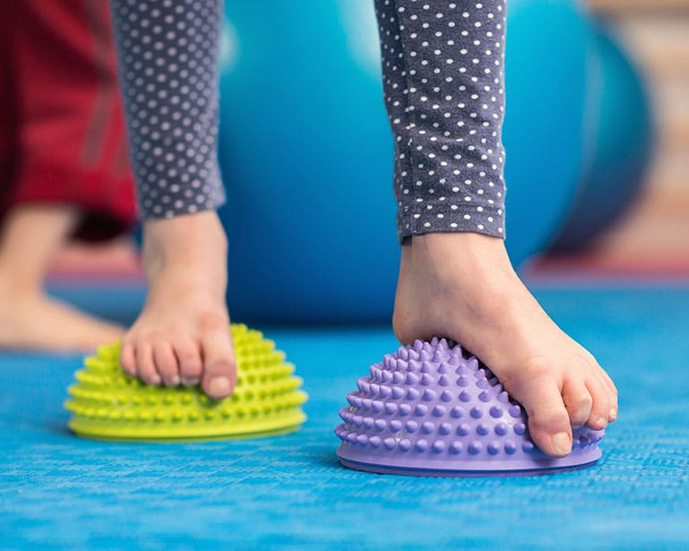 Kind bei Physiotherapiestunde stehend auf Balanceigeln